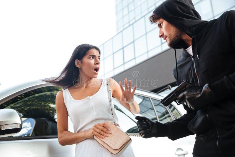 Εγκληματίας ανδρών που ληστεύει και που απειλεί με το πυροβόλο όπλο στην εκφοβισμένη γυναίκα στοκ εικόνες με δικαίωμα ελεύθερης χρήσης