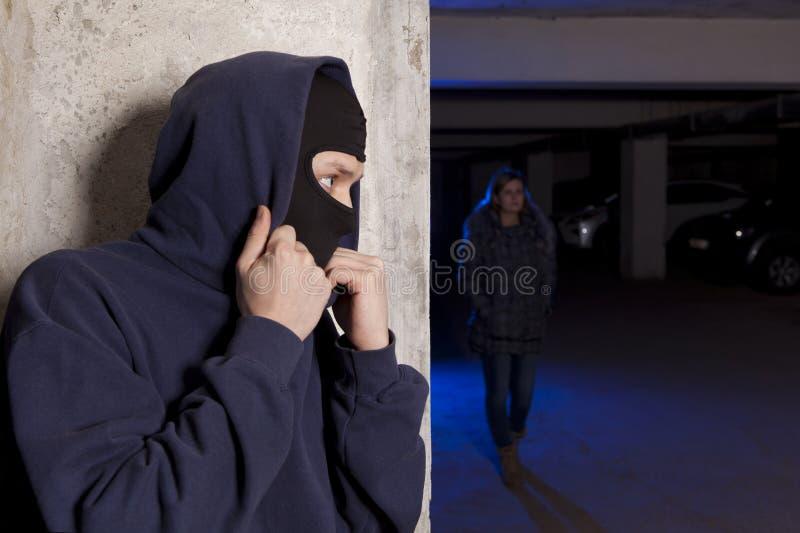 Εγκληματίας που φορά μια μάσκα που περιμένει μια γυναίκα στοκ εικόνες