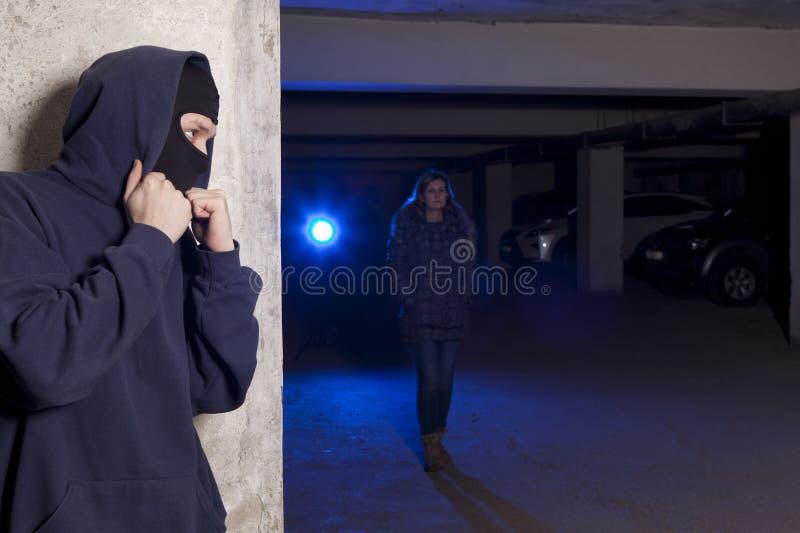Εγκληματίας που φορά μια μάσκα που περιμένει μια γυναίκα στοκ φωτογραφία