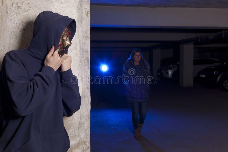 Εγκληματίας που φορά μια μάσκα που περιμένει μια γυναίκα στοκ φωτογραφίες