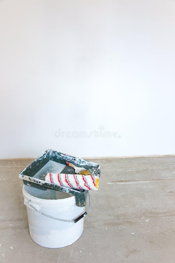 Εγχυτήρας που εφαρμόζεται στον τοίχο τσιμέντου Κενοί κάδος, βούρτσα και κύλινδρος LE στοκ εικόνες