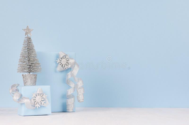 Εγχώρια διακόσμηση Χριστουγέννων - το ασημένιο έλατο με τα εορταστικά κιβώτια δώρων με τα σπινθηρίσματα υποκύπτει στον άσπρο ξύλι στοκ εικόνες