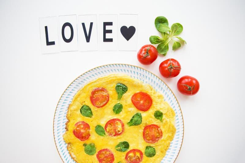 Εγχώρια κλασική ομελέτα με τις ντομάτες κερασιών και το βασιλικό, αγάπη επιγραφής στοκ εικόνα