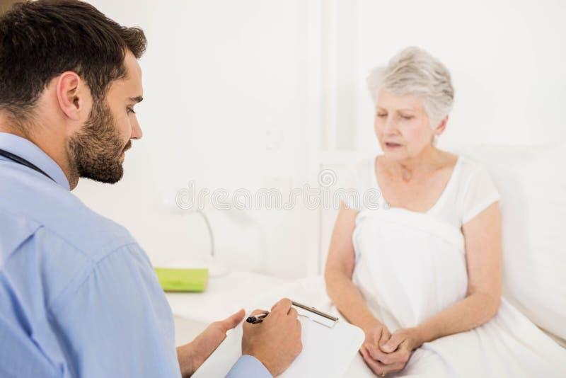 Εγχώρια νοσοκόμα που ακούει την ηλικιωμένη γυναίκα και που γράφει στην περιοχή αποκομμάτων στοκ εικόνες