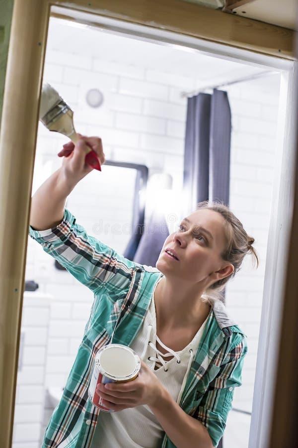 Εγχώριες επισκευές Μια γυναίκα χρωματίζει στο λευκό την είσοδο στο λουτρό με μια βούρτσα και μπορεί, την οποία κρατά στα χέρια τη στοκ φωτογραφία