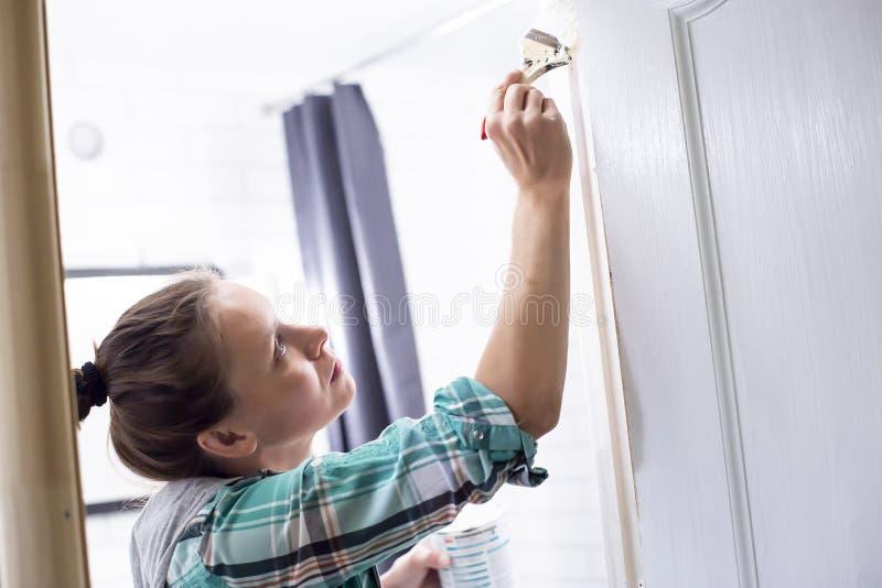 Εγχώριες επισκευές Μια γυναίκα χρωματίζει στο λευκό την είσοδο στο λουτρό με μια βούρτσα και μπορεί, την οποία κρατά στα χέρια τη στοκ εικόνες