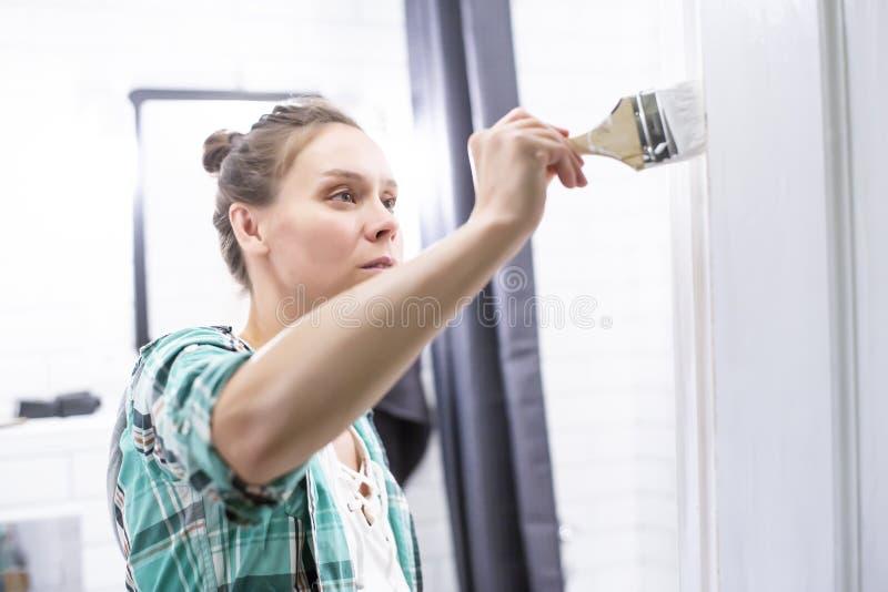 Εγχώριες επισκευές Μια γυναίκα χρωματίζει στο λευκό την είσοδο στο λουτρό με μια βούρτσα που κρατά στα χέρια της στοκ φωτογραφία