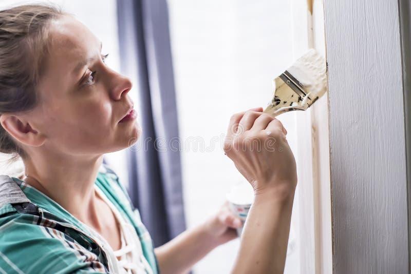 Εγχώριες επισκευές Μια γυναίκα χρωματίζει στο λευκό την είσοδο στο λουτρό με μια βούρτσα και μπορεί, την οποία κρατά στα χέρια τη στοκ φωτογραφίες με δικαίωμα ελεύθερης χρήσης