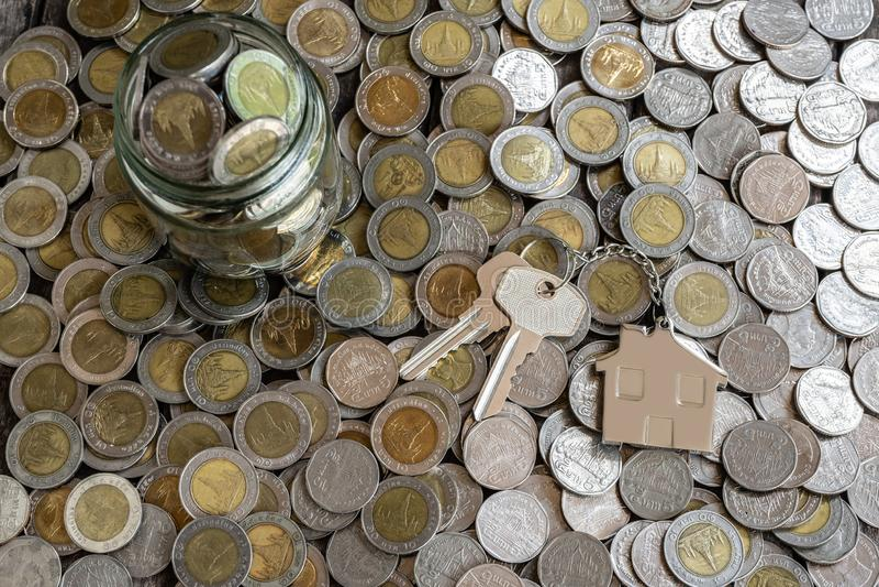 Εγχώριο κλειδί με το μπρελόκ σπιτιών στο υπόβαθρο σωρών νομισμάτων, επιχειρησιακή έννοια στοκ εικόνες
