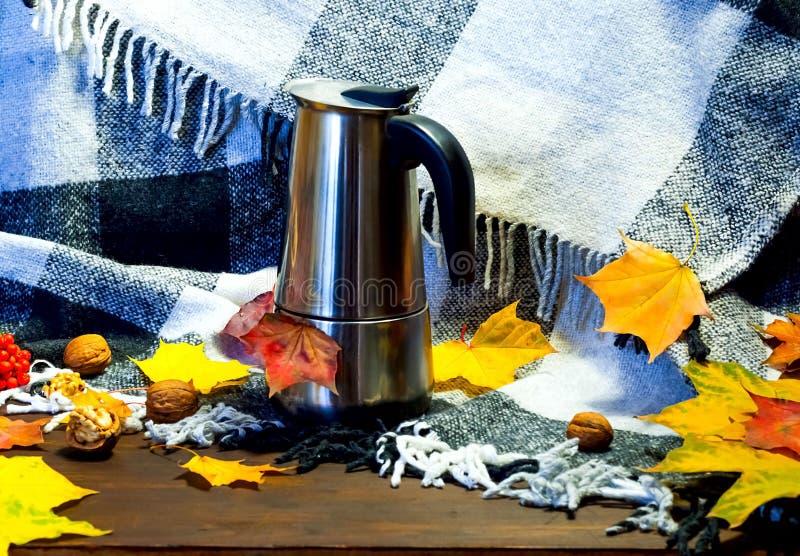 Εγχώριο ντεκόρ φθινοπώρου Μεταλλικό δοχείο καφέ ανάμεσα στα φωτεινά κίτρινα φύλλα στο υπόβαθρο των πλεκτών ενδυμάτων και του ελεγ στοκ φωτογραφία με δικαίωμα ελεύθερης χρήσης