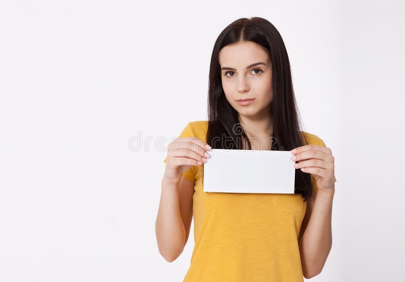 εδώ κείμενό σας Αρκετά νέα γυναίκα που κρατά τον κενό κενό πίνακα Πορτρέτο στούντιο στην άσπρη ανασκόπηση Πρότυπο για το σχέδιο στοκ φωτογραφία