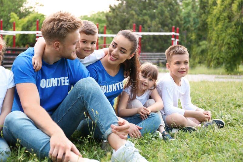 Εθελοντές και παιδιά που κάθονται στη χλόη στοκ εικόνες με δικαίωμα ελεύθερης χρήσης