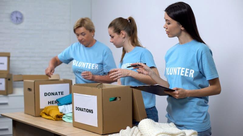 Εθελοντές που βάζουν ρούχα σε κουτιά δωρεάς, κοινωνικός λειτουργός που κάνει σημειώσεις φιλανθρωπία στοκ φωτογραφίες με δικαίωμα ελεύθερης χρήσης