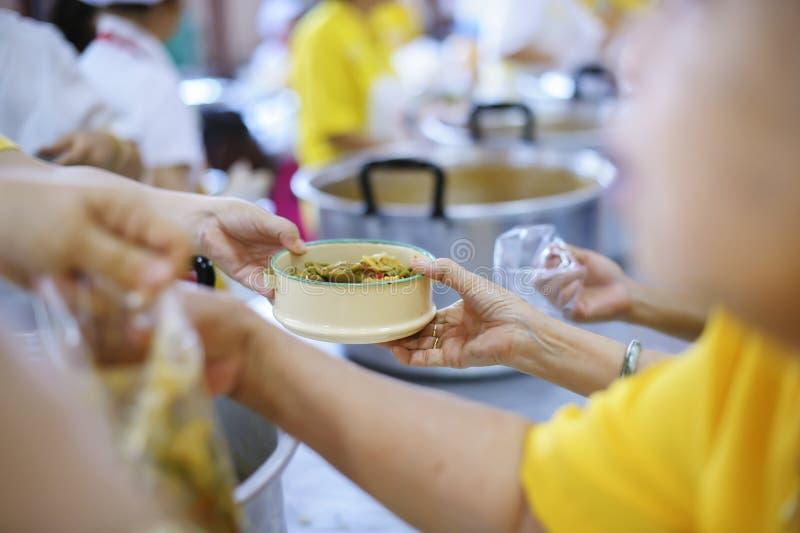 Εθελοντής για να ταΐσει τον πεινασμένο στην κοινωνία: Η έννοια να δώσει τα τρόφιμα στους φτωχούς στην κοινωνία στοκ εικόνες