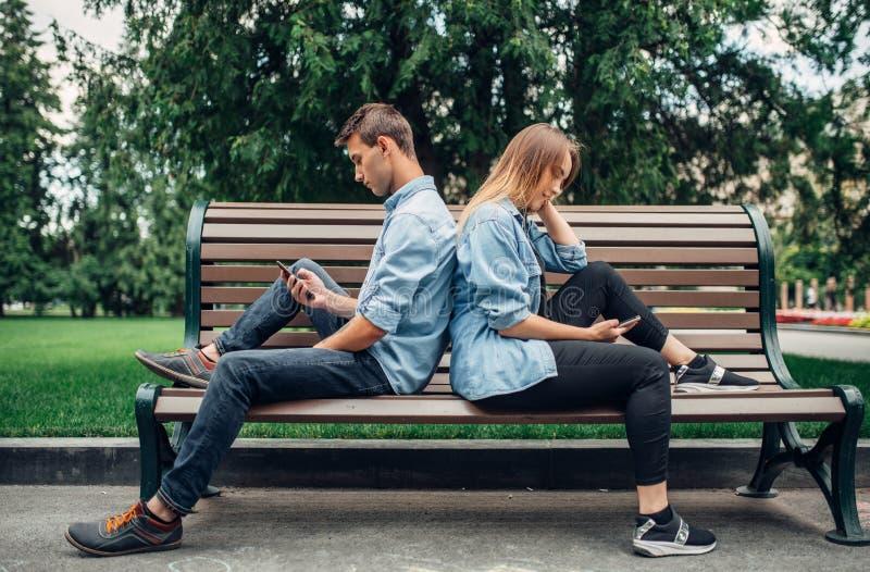 Εθισμένοι τηλέφωνο άνθρωποι, ζεύγος στον πάγκο στοκ φωτογραφία με δικαίωμα ελεύθερης χρήσης
