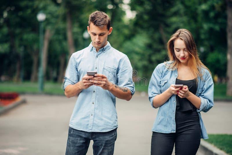 Εθισμένοι τηλέφωνο άνθρωποι, ζεύγος στο θερινό πάρκο στοκ φωτογραφία με δικαίωμα ελεύθερης χρήσης