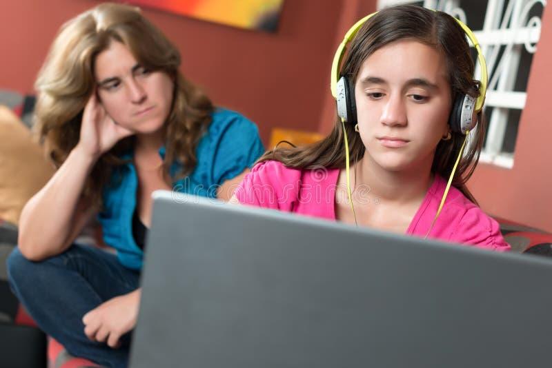 Εθισμένο το υπολογιστής κορίτσι αγνοεί την ανησυχημένη μητέρα της στοκ εικόνα