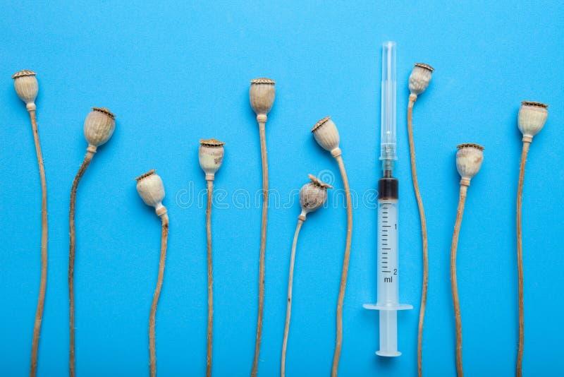 Εθισμός στα ναρκωτικά και η επεξεργασία του Φάρμακα, οπιούχος ουσία και ηρωίνη οπίου στο μπλε υπόβαθρο στοκ εικόνες