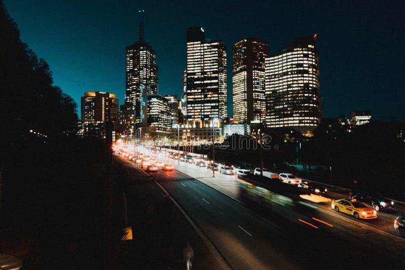 Εθνική οδός με τα μέρη των αυτοκινήτων τη νύχτα με τα ψηλά αναμμένα κτήρια τη νύχτα στο υπόβαθρο στοκ εικόνα με δικαίωμα ελεύθερης χρήσης