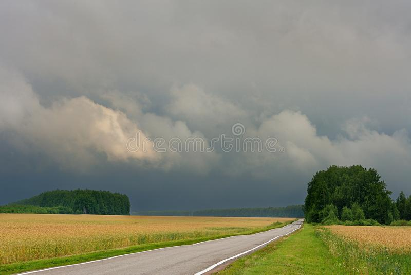 Εθνική οδός στους τομείς σίτου και τα σκοτεινά σύννεφα θύελλας στοκ εικόνες με δικαίωμα ελεύθερης χρήσης