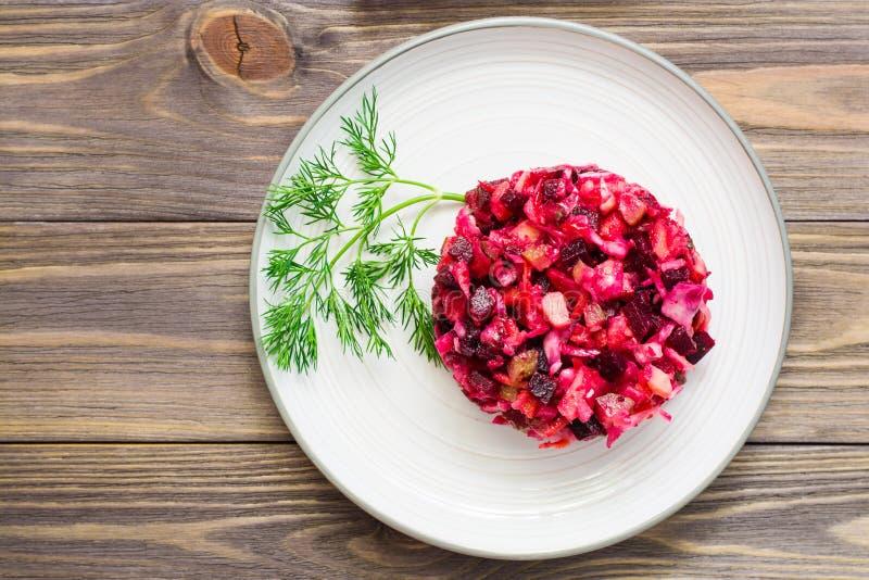 Εθνική ρωσική σαλάτα - vinaigrette - από τα βρασμένα λαχανικά, sauerkraut και τα παστωμένα αγγούρια σε ένα πιάτο σε έναν ξύλινο π στοκ φωτογραφία με δικαίωμα ελεύθερης χρήσης