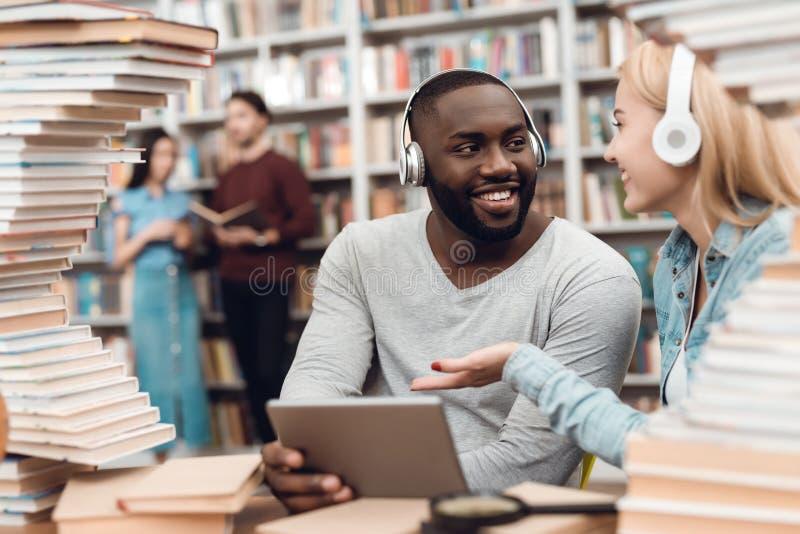 Εθνικός τύπος αφροαμερικάνων και λευκό κορίτσι που περιβάλλονται από τα βιβλία στη βιβλιοθήκη Οι σπουδαστές χρησιμοποιούν την ταμ στοκ εικόνα