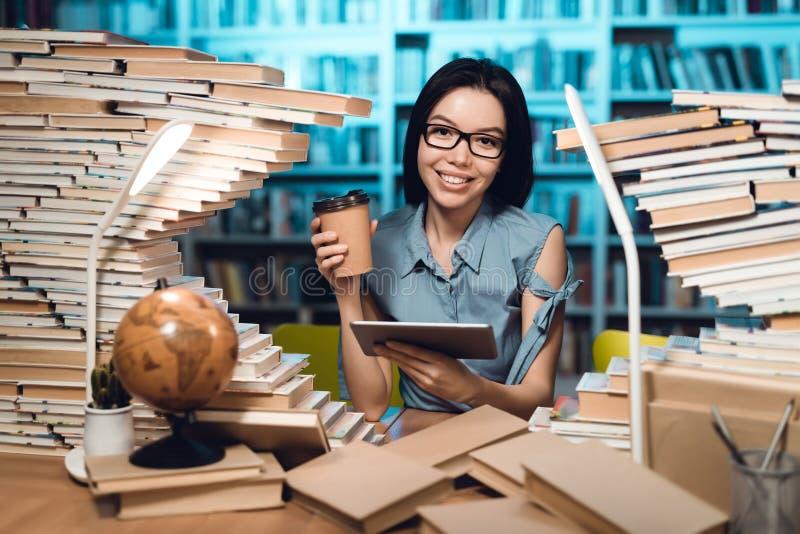 Εθνικό ασιατικό κορίτσι που περιβάλλεται από τα βιβλία στη βιβλιοθήκη τη νύχτα Ο σπουδαστής χρησιμοποιεί την ταμπλέτα στοκ εικόνα με δικαίωμα ελεύθερης χρήσης