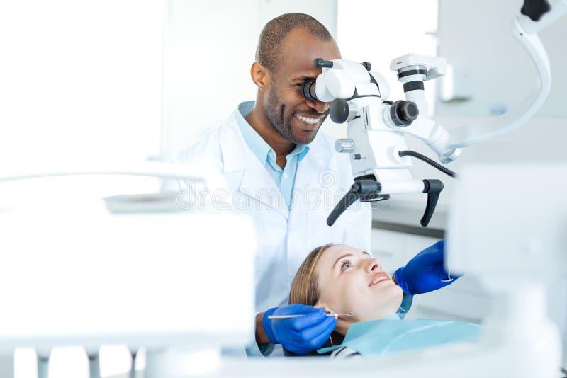 Ειδικευμένος οδοντίατρος που ενισχύει τα δόντια ασθενών του με το μικροσκόπιο στοκ εικόνα
