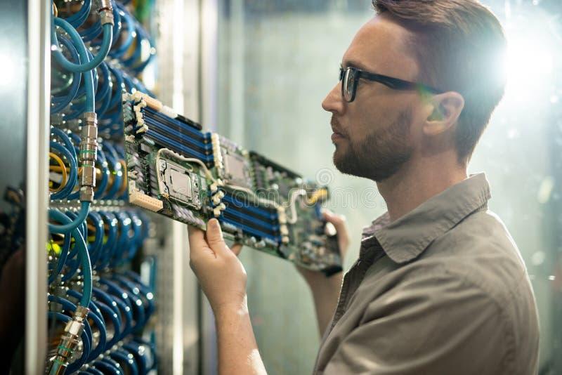 Ειδικός εγκαταστάσεων κεντρικών υπολογιστών που εργάζεται στο δωμάτιο datacenter στοκ εικόνα