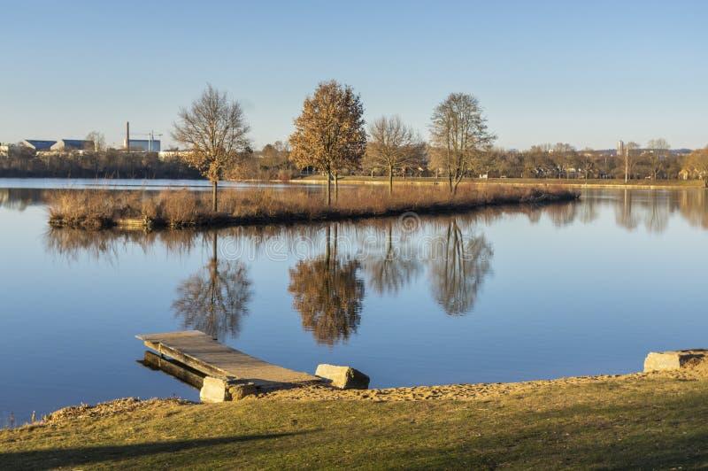 Ειδυλλιακή λίμνη με τις εγκαταστάσεις ελεύθερου χρόνου και την ψυχαγωγική περιοχή την άνοιξη με τις γειτονεύοντας με διανομές στοκ εικόνα