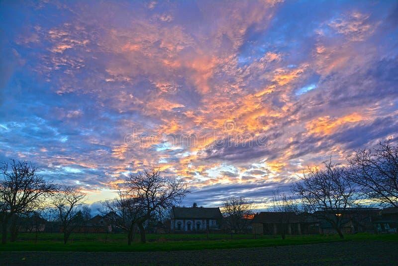 Ειδυλλιακή ύπαιθρος ηλιοβασίλεμα με δέντρο και σπίτι στοκ εικόνες