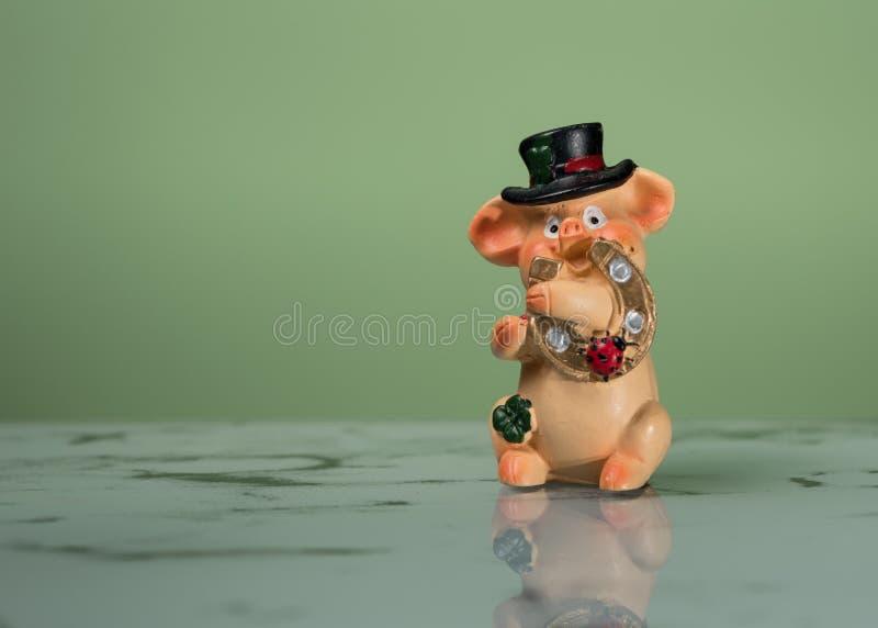 Ειδώλιο μικρού ενός piggy με ένα μαύρο καπέλο και ένα πέταλο στοκ εικόνα