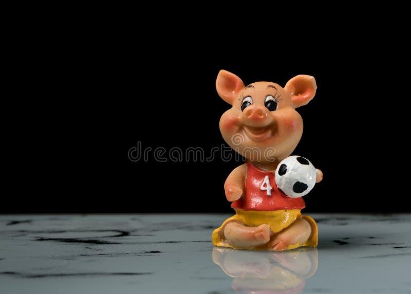 Ειδώλιο μικρού ενός piggy με ένα ποδόσφαιρο σε το χέρι ` s στοκ φωτογραφίες