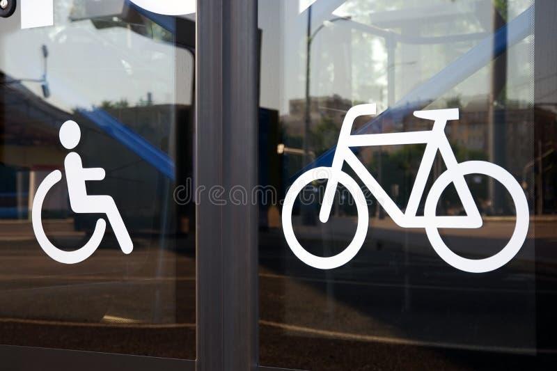 Εικονίδια για το με ειδικές ανάγκες άτομο και το ποδήλατο στις πόρτες λεωφορείων γυαλιού, κινηματογράφηση σε πρώτο πλάνο στοκ εικόνα