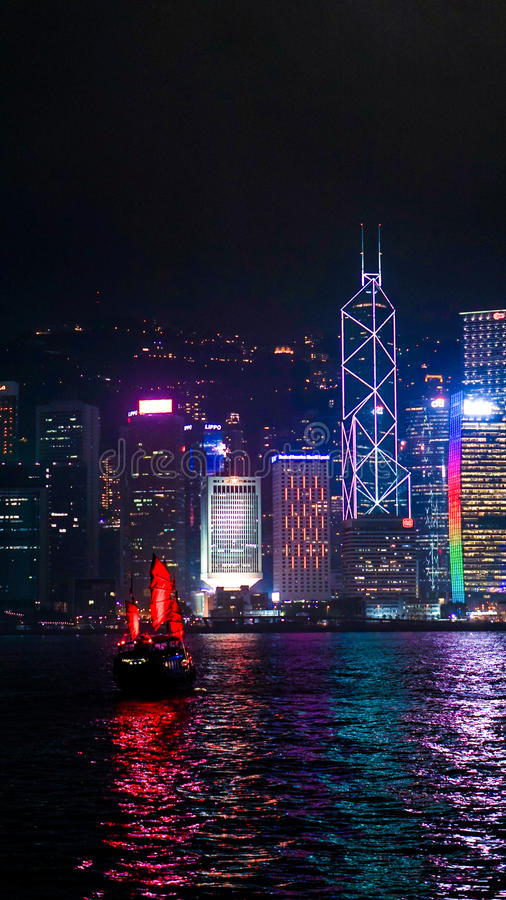 Εικονική κόκκινη εκλεκτής ποιότητας βάρκα πανιών Χονγκ Κονγκ που πλέει τη νύχτα τον ορίζοντα στοκ εικόνες