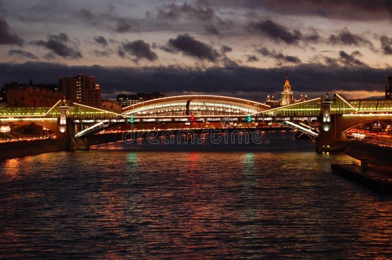 Εικονική παράσταση πόλης νύχτας έναν ποταμό και μια γέφυρα που διακοσμούνται με με τα φανάρια στοκ φωτογραφία