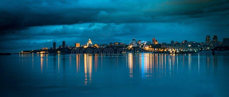 Εικονική παράσταση πόλης: Τα φω'τα της πόλης νύχτας στον ορίζοντα απεικονίζονται στο ομαλό νερό στοκ εικόνα με δικαίωμα ελεύθερης χρήσης