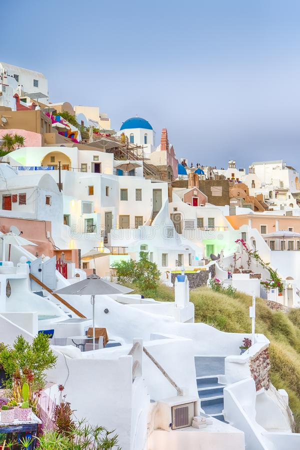 Εικονική παράσταση πόλης Oia του χωριού στο νησί Santorini με Caldera τα βουνά στο υπόβαθρο στις ακτίνες της ρύθμισης του ήλιου στοκ εικόνα με δικαίωμα ελεύθερης χρήσης