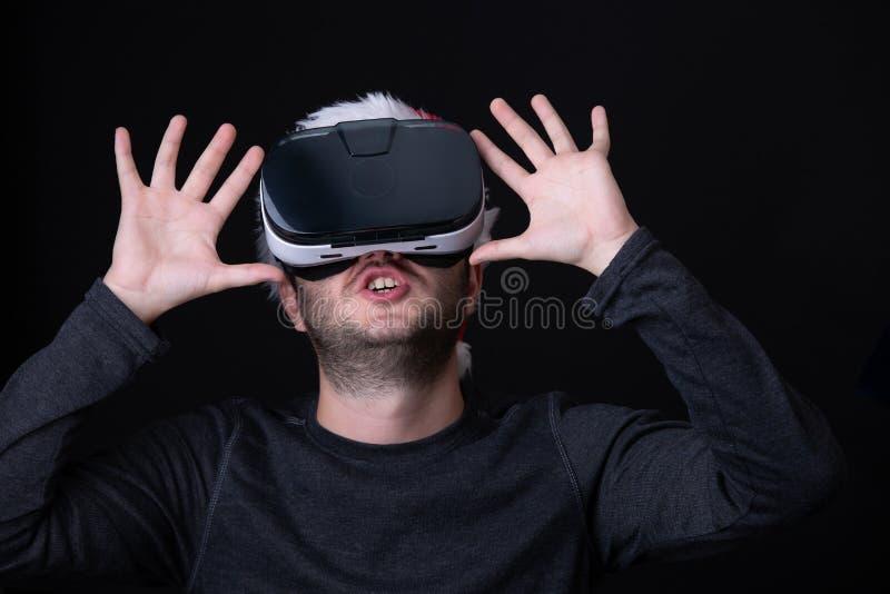 Εικόνα έκπληκτος brunet στην ΚΑΠ Santa και γυαλιά της εικονικής πραγματικότητας στοκ φωτογραφία με δικαίωμα ελεύθερης χρήσης