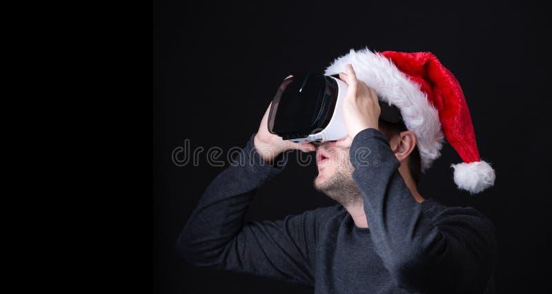 Εικόνα έκπληκτος brunet στην ΚΑΠ Santa και των γυαλιών της εικονικής πραγματικότητας στοκ φωτογραφίες με δικαίωμα ελεύθερης χρήσης
