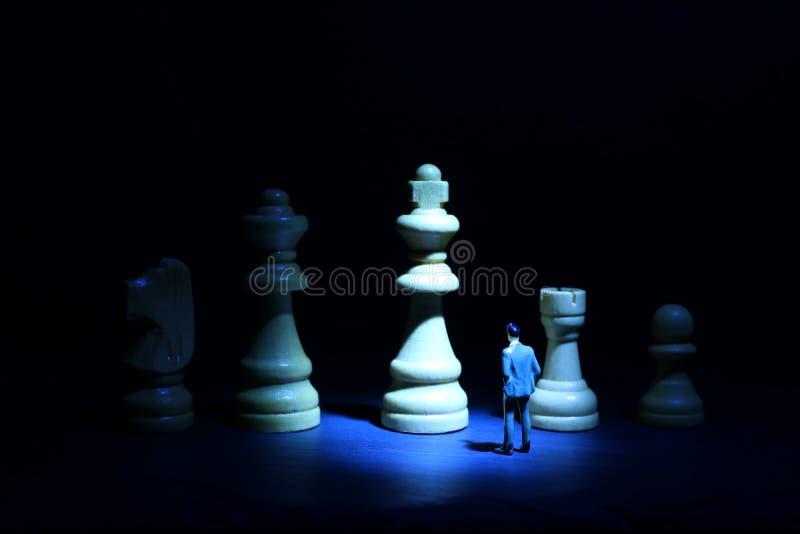 Εικόνα έννοιας ενός επιχειρηματία που εξετάζει τους αριθμούς σκακιού και που σκέφτεται για ένα σχέδιο δράσης στοκ φωτογραφίες