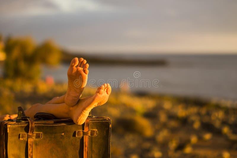 Εικόνα έννοιας ταξιδιού η παραλία και ο ωκεανός μέσα backgorund και coulpe των θηλυκών nude ποδιών στις παλαιές εκλεκτής ποιότητα στοκ φωτογραφίες