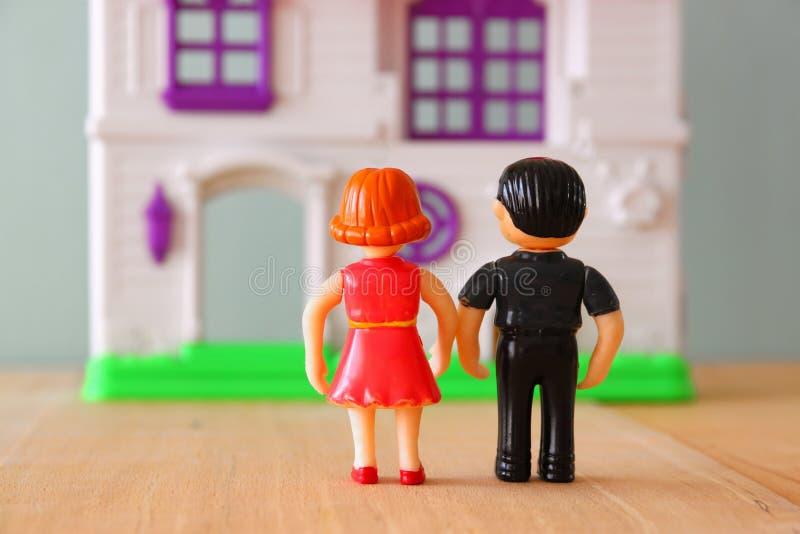 Εικόνα έννοιας του νέου ζεύγους μπροστά από το καινούργιο σπίτι κούκλες λίγων πλαστικές παιχνιδιών (αρσενικό και θηλυκό), εκλεκτι στοκ φωτογραφίες