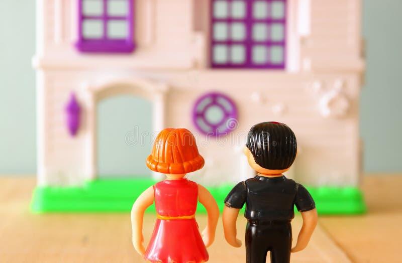 Εικόνα έννοιας του νέου ζεύγους μπροστά από το καινούργιο σπίτι κούκλες λίγων πλαστικές παιχνιδιών (αρσενικό και θηλυκό), εκλεκτι στοκ φωτογραφία