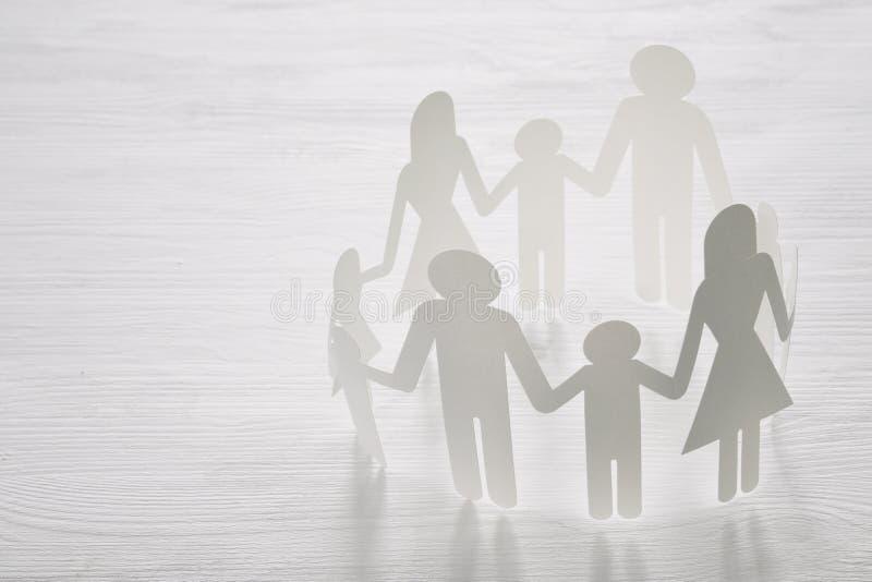 εικόνα έννοιας των χεριών εκμετάλλευσης διακοπής αλυσίδων οικογενειακού εγγράφου, πέρα από τον ξύλινο πίνακα στοκ εικόνα