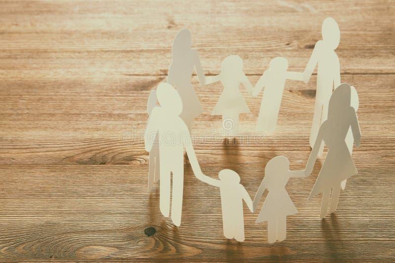 εικόνα έννοιας των χεριών εκμετάλλευσης διακοπής αλυσίδων οικογενειακού εγγράφου, πέρα από τον ξύλινο πίνακα στοκ εικόνα με δικαίωμα ελεύθερης χρήσης
