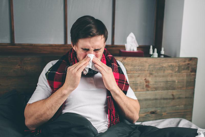 Εικόνα από έναν νεαρό άνδρα με το χαρτομάνδηλο Ο άρρωστος τύπος βρίσκεται στο κρεβάτι και έχει τη runny μύτη το άτομο κάνει μια θ στοκ φωτογραφίες