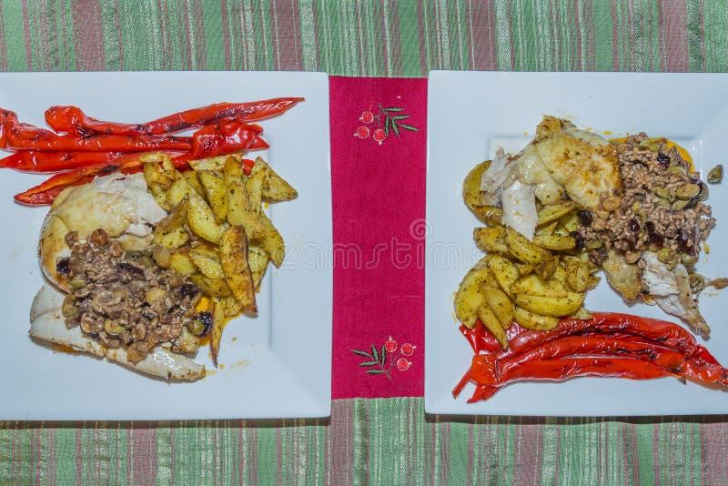 Εικόνα δύο άσπρων πιάτων κάθε ένα με ένα κομμάτι του κοτόπουλου, που γεμίζει με το επίγειο βόειο κρέας με τις ελιές, τις σταφίδες στοκ φωτογραφία