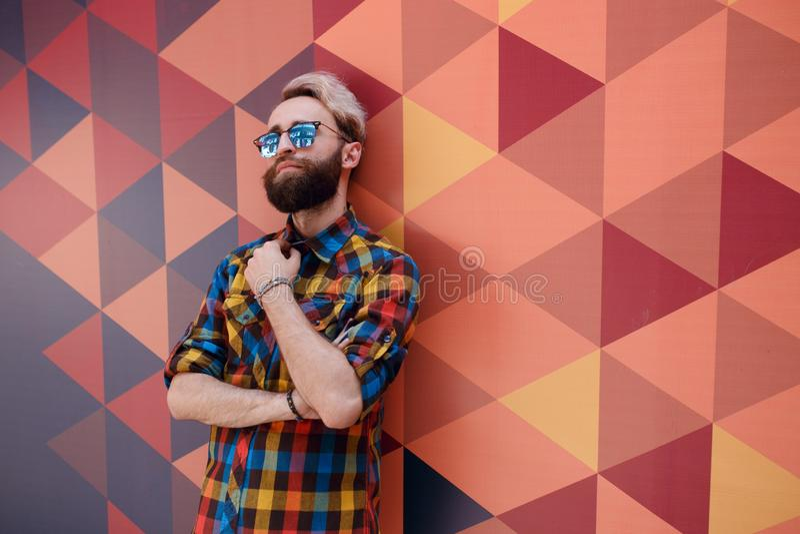 Εικόνα ενός μοντέρνου νέου προτύπου, που ντύνεται σε μια πολύχρωμη μπλούζα, που θέτει hexagons γεωμετρικός τοίχος μορφής στοκ εικόνα
