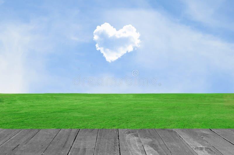 Εικόνα ενός σύννεφου καρδιών στο μπλε ουρανό στον πράσινο τομέα και το ξύλινο pla στοκ φωτογραφία με δικαίωμα ελεύθερης χρήσης